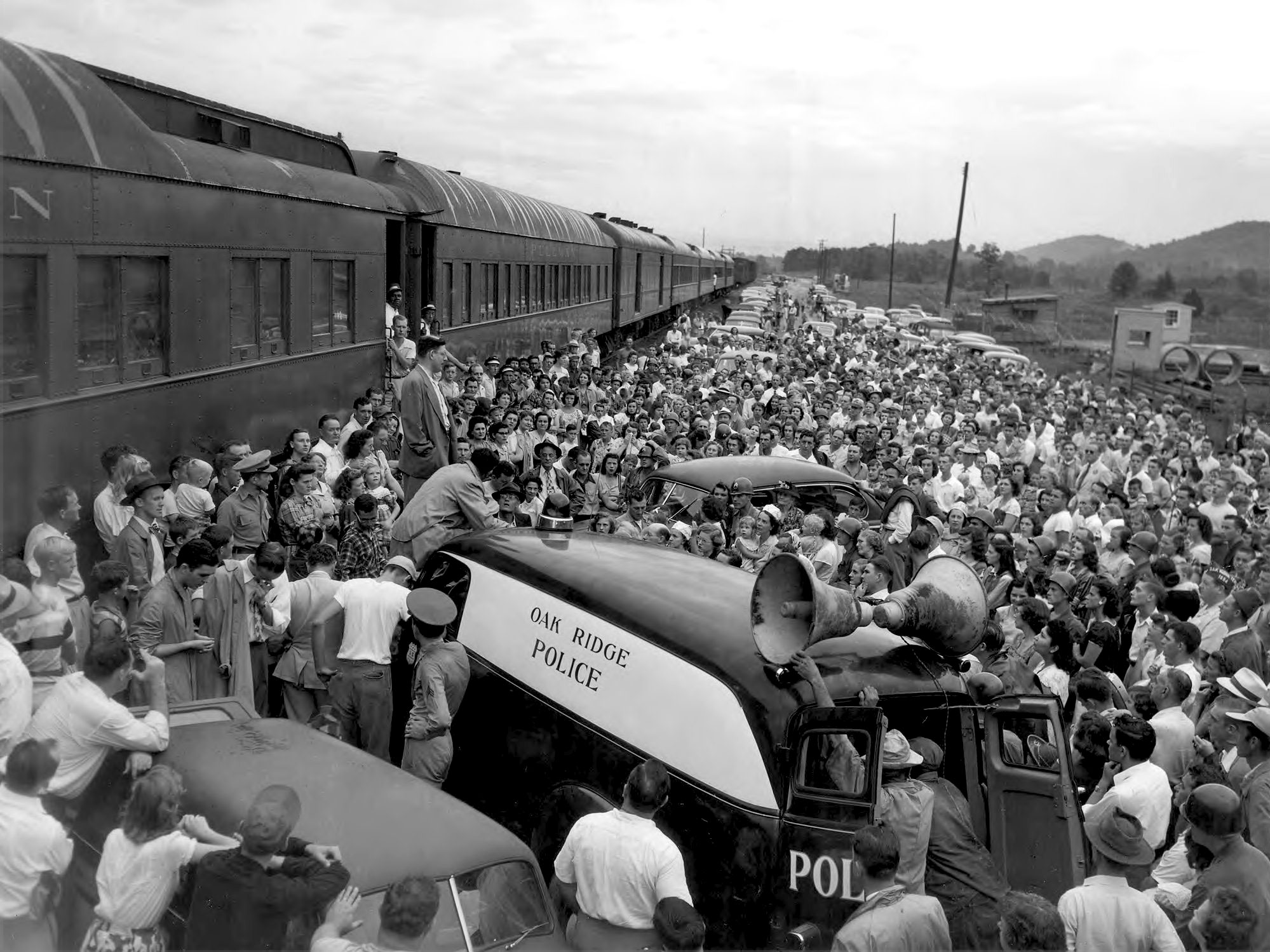 """A wounded soldier speaks to a large crowd in front of a train. An automobile with a loudspeaker mounted on top is nearby and is labeled """"Oak Ridge Police. Circa 1944."""