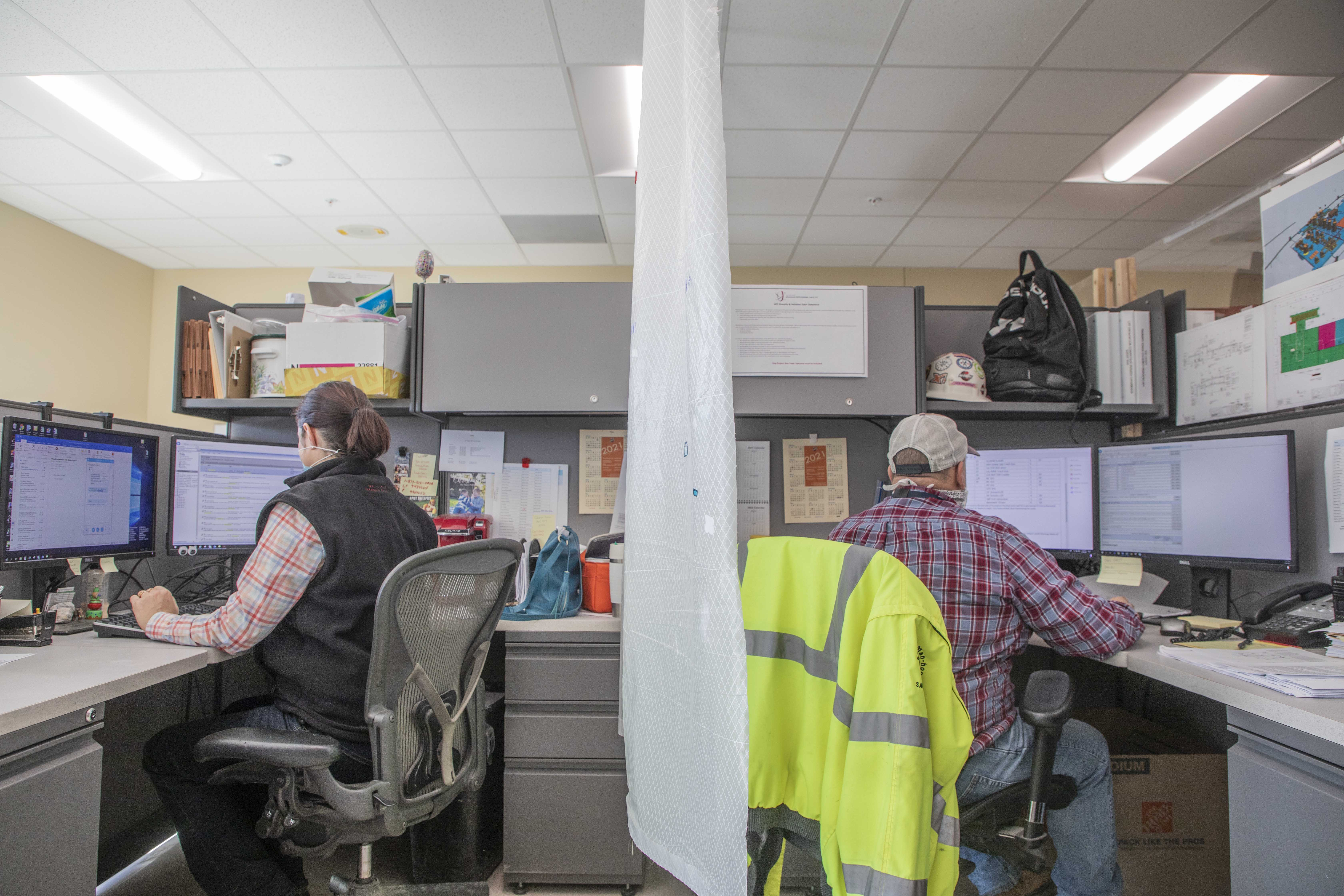 Two mission essential UPF employees work back to back with a COVID-19 safety partition between to maximize social distancing.