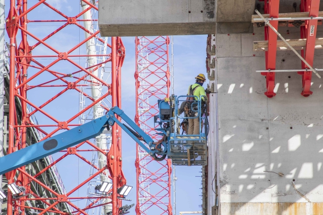UPF ironworker inspects a second elevation concrete wall on the Main Process Building.