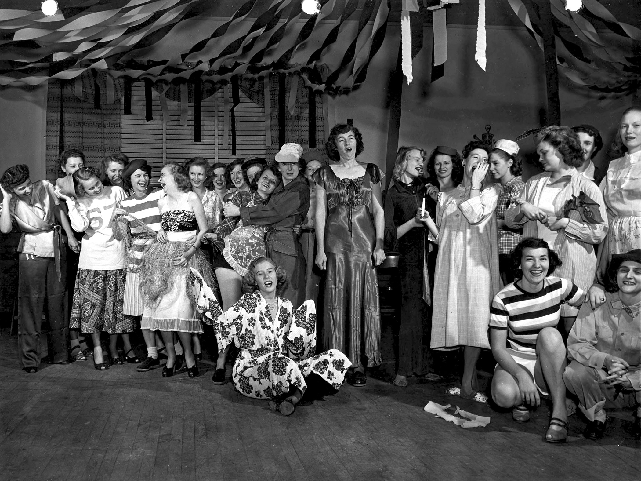 A large group of women wear costumes, perhaps for a skit or a party. Streamers hang from the ceiling. Circa 1947.