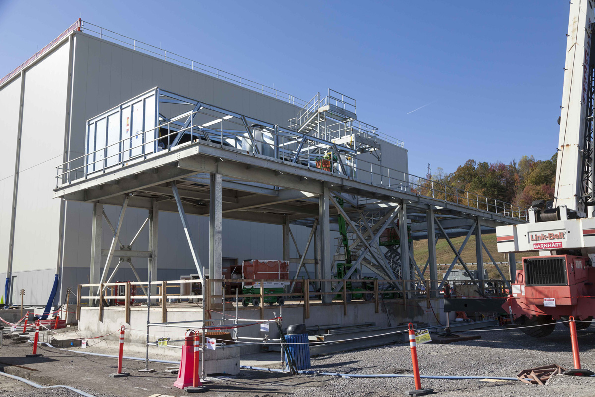 The cooling tower continues to rise next to the Uranium Processing Facility Mechanical and Electrical Building.