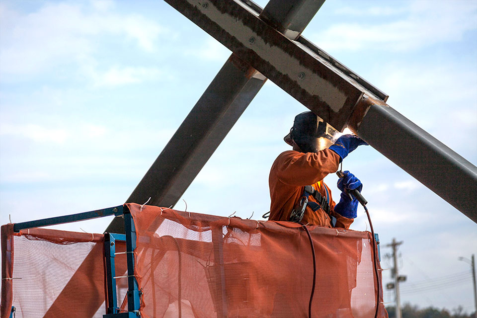 A welder works on the cross bracing for the Mechanical Electrical Building (MEB) structure. MEB was the first of UPF's three main facilities to go vertical.