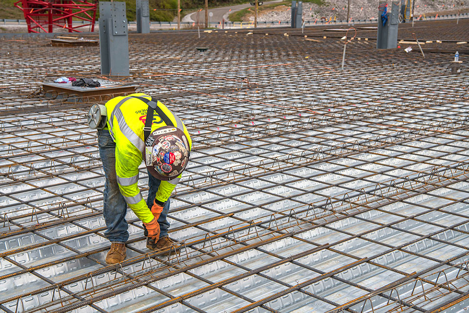 An ironworker ties rebar on the second level of the Mechanical Electrical Building in preparation for elevated concrete placement and structural steel for the second floor.