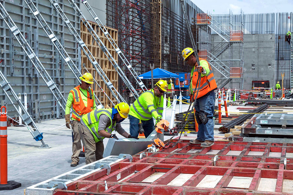 Carpenters assemble wall formwork sections before lifting them into place at the Main Process Building.