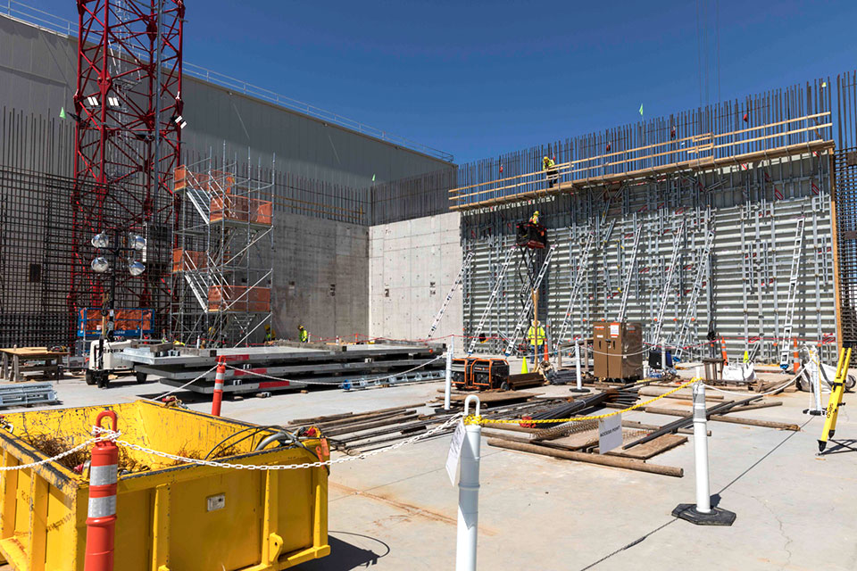 Now that the first vertical wall has been placed at the Main Process Building, additional forms are added on to the inside and outside of the rebar wall curtain to prepare for the next concrete placements.