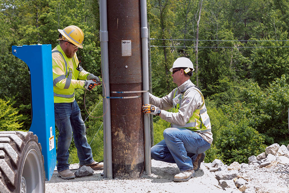 Ground wire installation takes place on a communications line at the Uranium Processing Facility Substation.