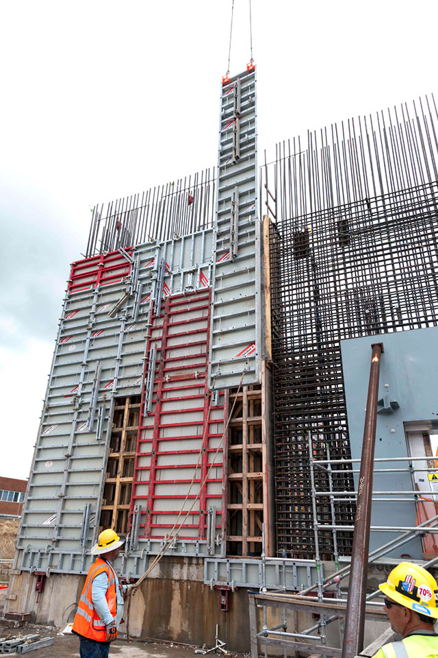 Forms are installed on the outside of a rebar wall curtain at the Main Process Building (MPB). Once inside and outside forms are installed, concrete is placed to construct the outside wall of the MPB.