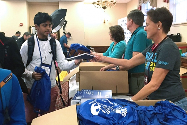 Pantex's Darla Fish greets an Ascension Academy student as teams check in for the National Science Bowl® at the National 4-H Youth Conference Center in Maryland.