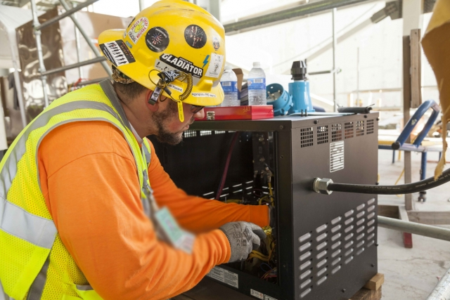 A Uranium Processing Facility (UPF) team member works on the setup of Construction power in the UPF Salvage and Accountability Building.
