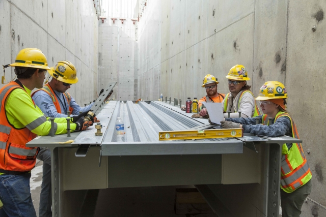 A Uranium Processing Facility team meeting is held in a Main Process Building corridor.