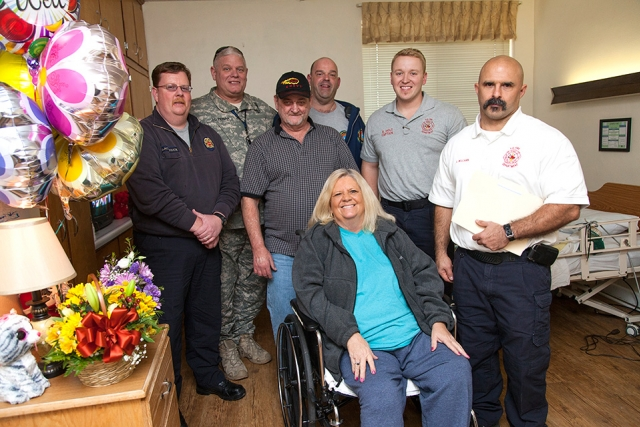 The Y-12 Fire Department paramedics and Security Police Officer who gave Freida Williford, front, lifesaving CPR visited her and her husband at the Harriman Care and Rehabilitation Center. From left behind her are, Justin Blackstock, Joe Perian, Keith Williford, Rick Dettmering, Brad Holt and Loyd Williams.