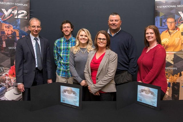 Consolidated Nuclear Security, LLC President and CEO Morgan Smith (left) joins CEO Cindy Hatfield (front center) and employees of Hatfield Constructions after signing a mentor-protégé agreement.