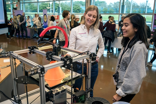 "At the Y-12 National Security Complex's Introduce a Girl to Engineering event last week, Téa Phillips, left, demonstrates a 3D printer to Lesly, an Oak Ridge High School senior. ""I like talking to the girls, getting them interested in engineering and Y-12,"" said Phillips, a mechanical engineer and recent Y-12 hire. ""I've always wanted to work on something important, something where I can make a difference. I've found that work at Y-12, and I'm sharing that message with these girls."""