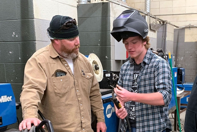 Y-12 National Security Complex welder Travis Scott (left) and Anderson County Career and Technical Center student Aaron discuss how to replace welding torch components and troubleshoot issues that could lead to poor welding performance.
