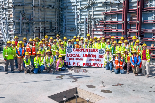 Carpenters on the Construction crew gather to celebrate the completion of first level walls at the Uranium Processing Facility Main Process Building.