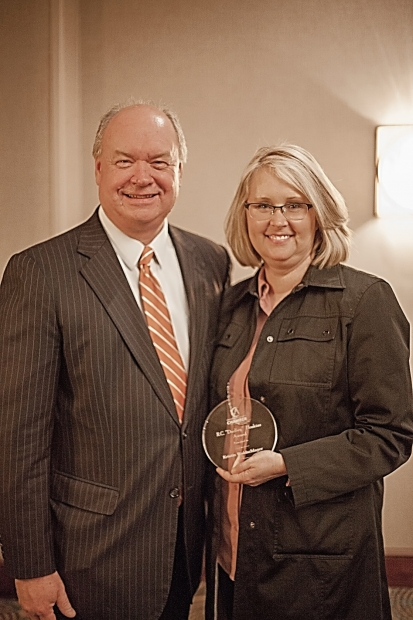 Chamber President Rick Meredith congratulates Waldschlager at the February 9 luncheon.