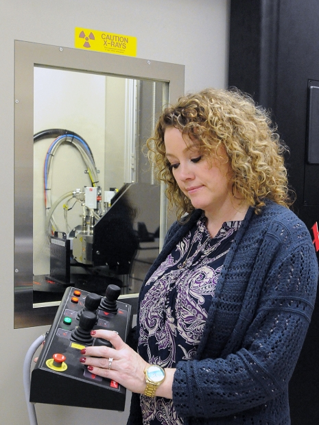 Pantex's Felicia Bellis uses controls to move a turntable of the microfocus X-ray machine, one of many technologies Pantex technicians use to ensure quality.