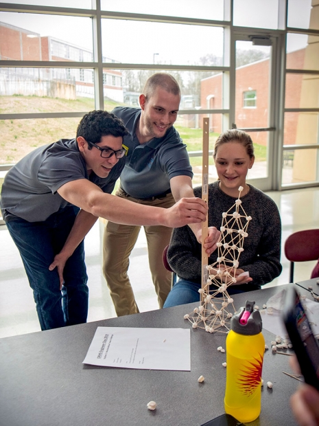 Matthew Chapa and a fellow engineer measure a student's tower during EWeek activities at ORHS.